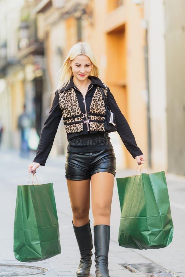 Lycklig härlig ung blond flicka som rymmer två dokument med olika förslagpackar royaltyfri fotografi