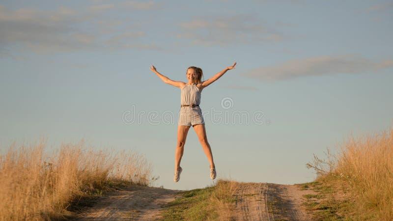Lycklig härlig ung flickadans i ett fält royaltyfria foton