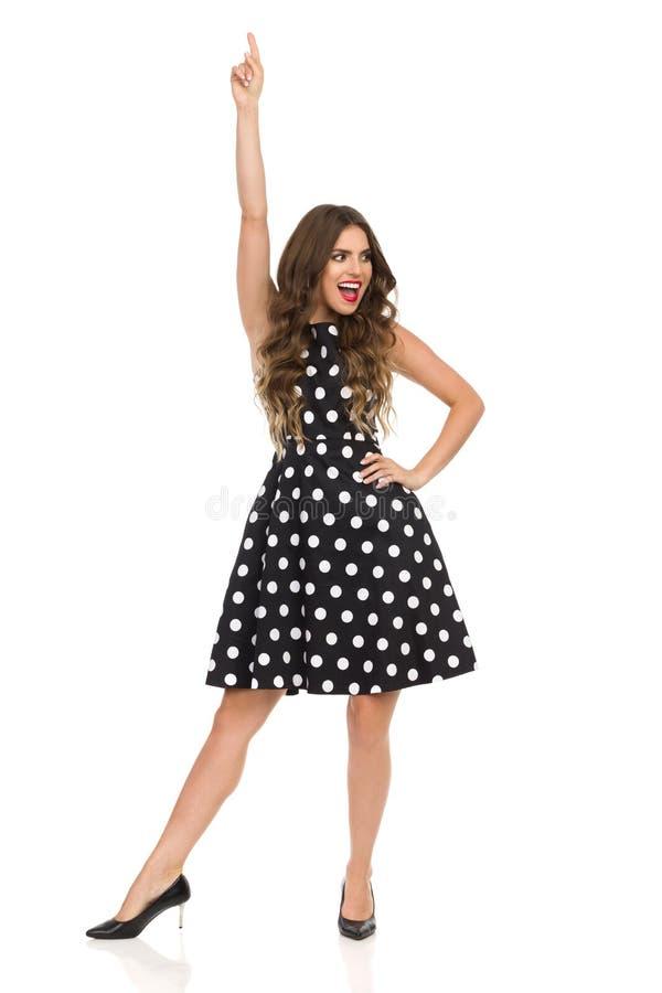 Lycklig härlig ung kvinna i svart coctailklänning i polkan Dots And High Heels Is som pekar upp och ropar royaltyfria bilder