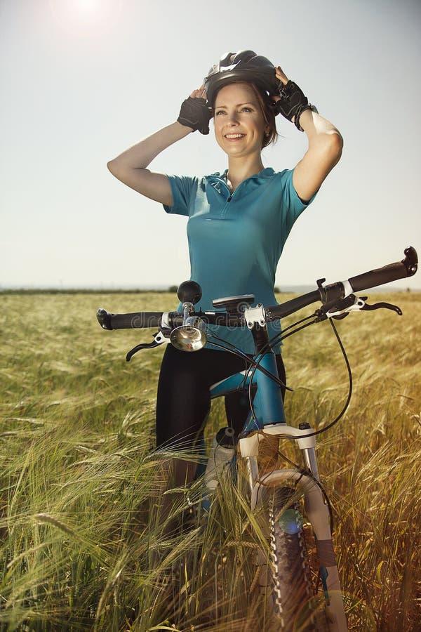 Lycklig härlig ung kvinna med en cykel på ett fält som rymmer hennes H royaltyfri fotografi
