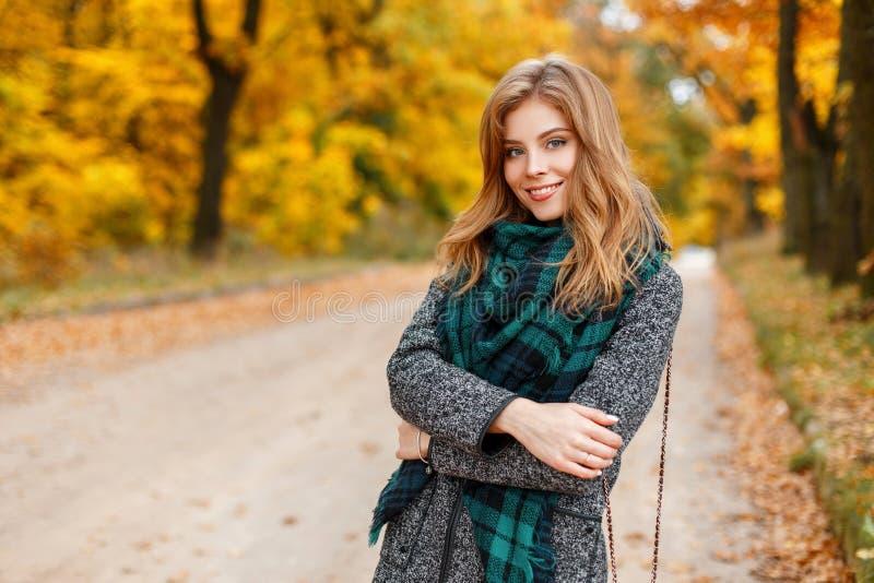 Lycklig härlig ung kvinna med ett charmigt leende i ett trendigt höstlag med en stilfull grön halsduk med en läderhandväska royaltyfria foton