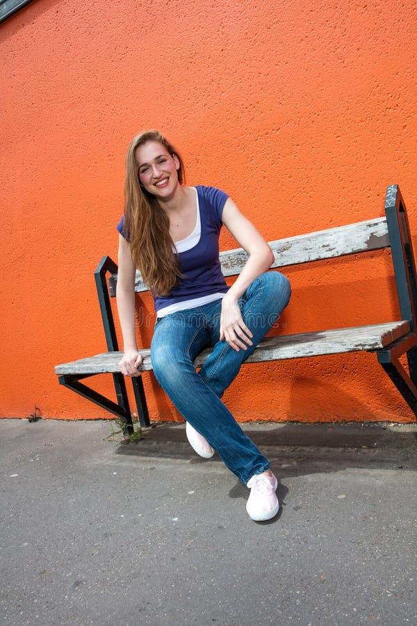 Lycklig härlig ung kvinna med korsade ben som tycker om det soliga avbrottet royaltyfria bilder