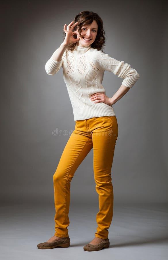 Lycklig härlig ung kvinna som visar det reko tecknet fotografering för bildbyråer