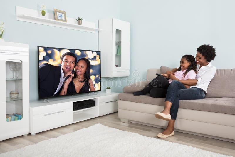 Lycklig hållande ögonen på television för moder och för dotter arkivbilder
