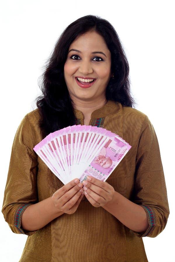 Lycklig hållande indier för ung kvinna 2000 rupieanmärkningar royaltyfria foton