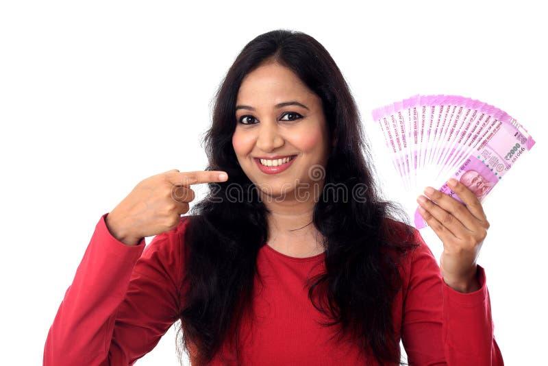 Lycklig hållande indier för ung kvinna 2000 rupieanmärkningar arkivbild