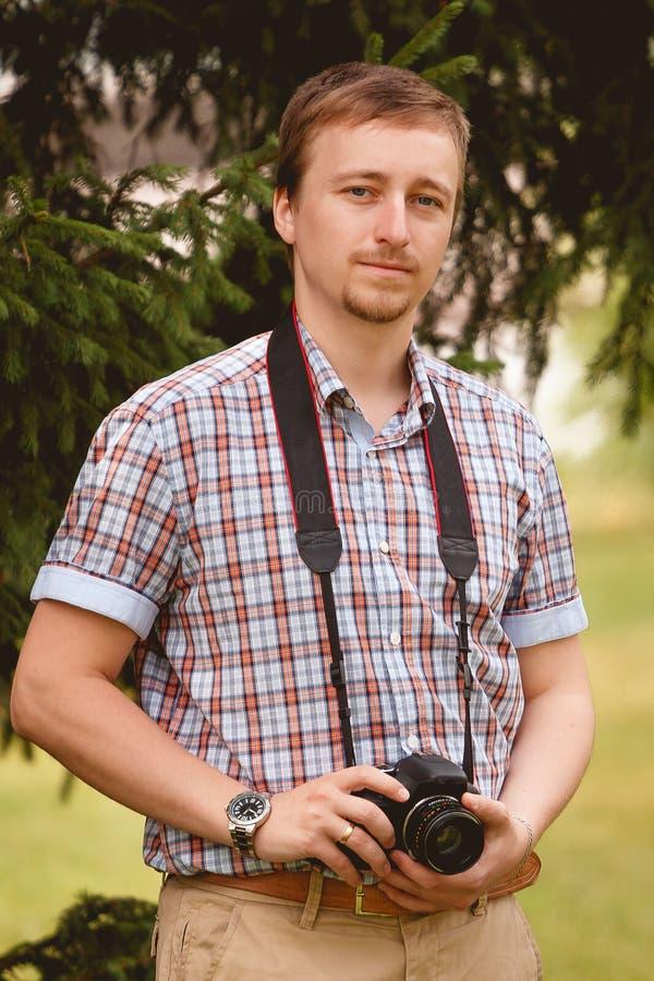 Lycklig hållande kamera för ung man som tar fotofotografen arkivfoton