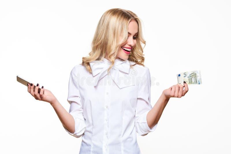 Lycklig hållande mobiltelefon för ung kvinna och en sedel för euro som fem ler med spänning Billig telefonräkning, internetshoppi royaltyfri foto