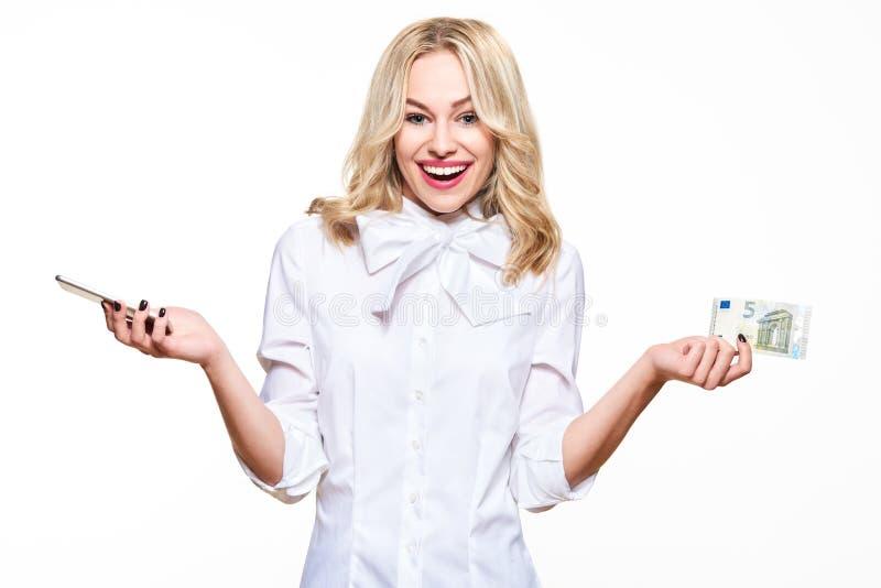 Lycklig hållande mobiltelefon för ung kvinna och en sedel för euro som fem ler med spänning Billig telefonräkning, internetshoppi royaltyfri bild