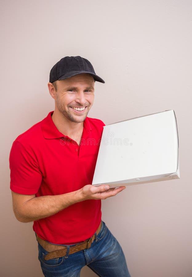 Lycklig hållande pizza för leveransman fotografering för bildbyråer
