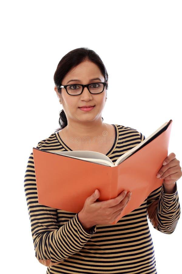 Lycklig hållande textbok för kvinnlig student royaltyfri foto