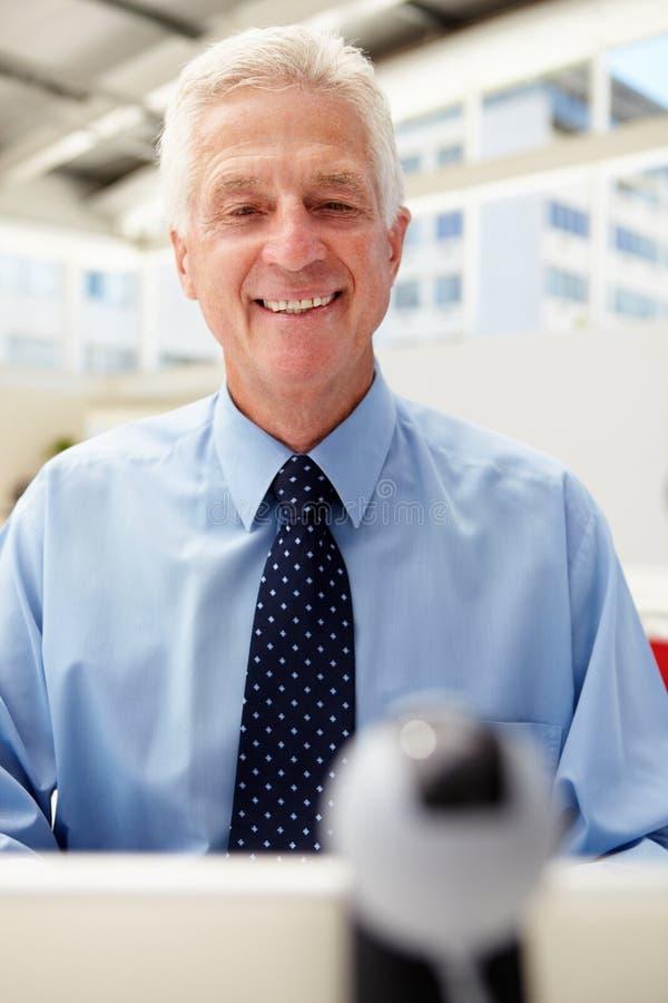 Lycklig hög affärsman som använder Skype royaltyfri bild