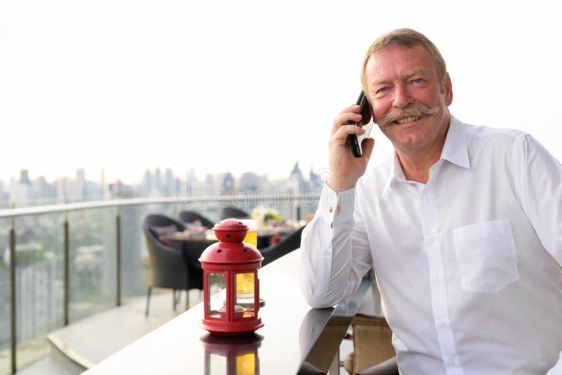Lycklig hög affärsman som ler, medan kalla med telefonen på takrestaurangen arkivbild