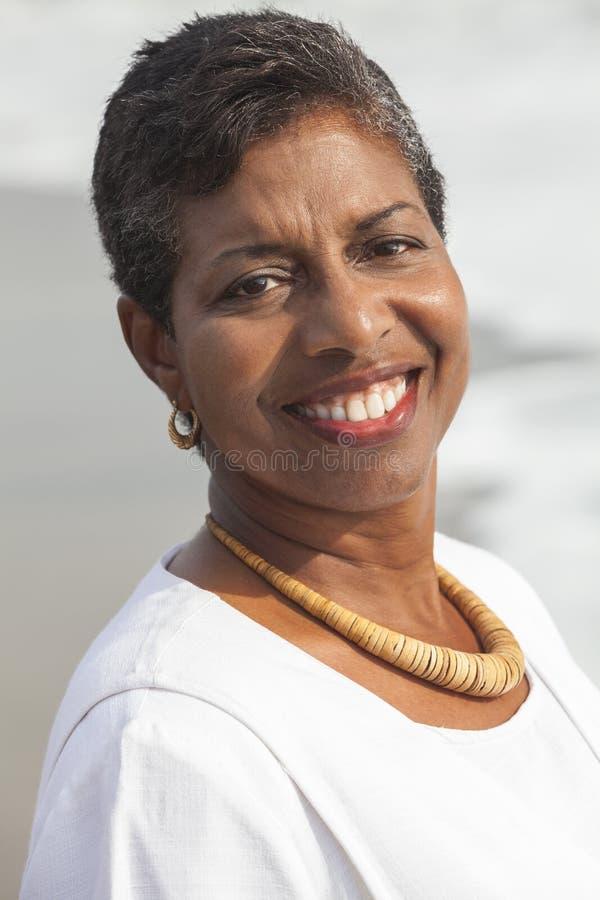 Lycklig hög afrikansk amerikankvinna på stranden royaltyfri foto