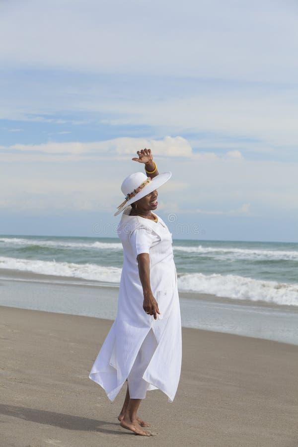 Lycklig hög afrikansk amerikankvinnadans på stranden royaltyfria bilder
