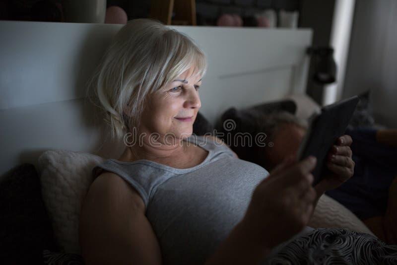 Lycklig hög dam som använder minnestavlan i säng royaltyfri foto