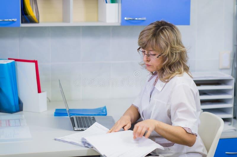 Lycklig hög doktor med skrivplattan på sjukhusmottagandet royaltyfri fotografi