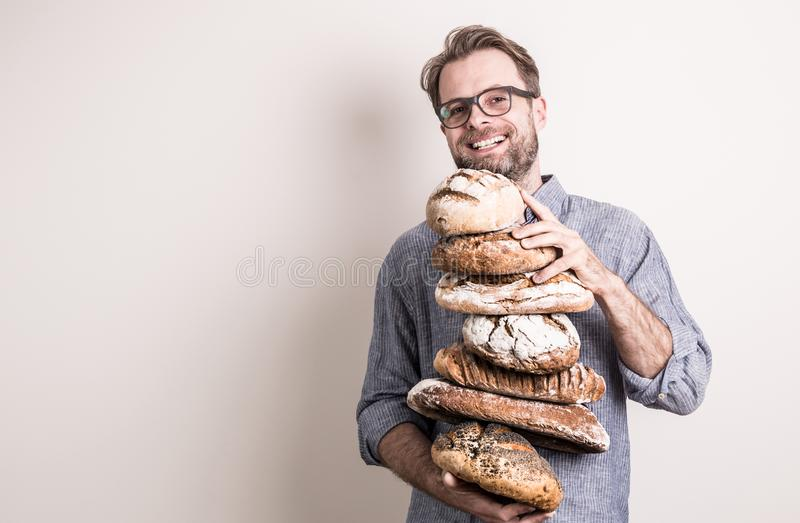 Lycklig hög för bagaremaninnehav av lantliga vresiga bröd arkivbilder