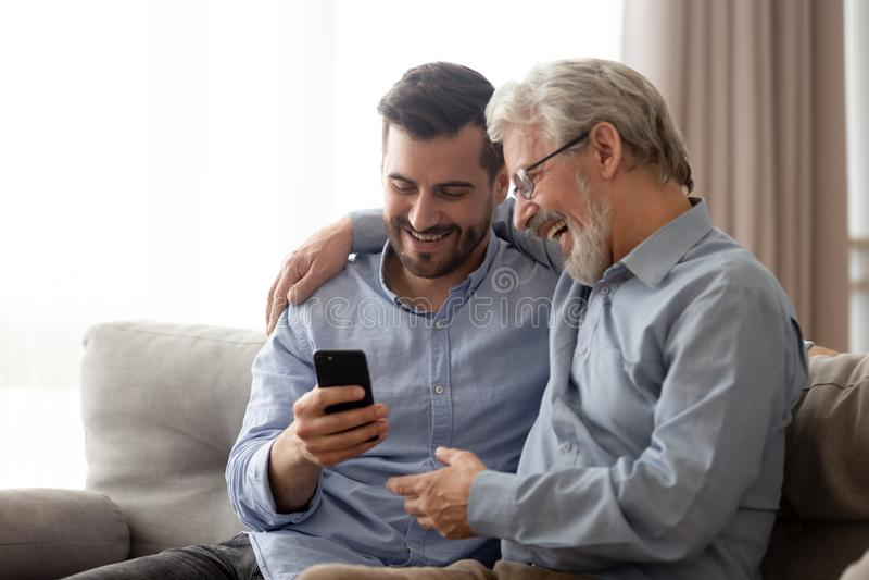 Lycklig h?g farsa och millennial son som tillsammans anv?nder smartphonen royaltyfria foton