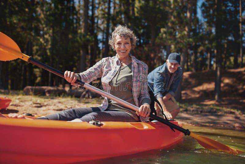 Lycklig hög kvinna i en kajak på sjön royaltyfri foto