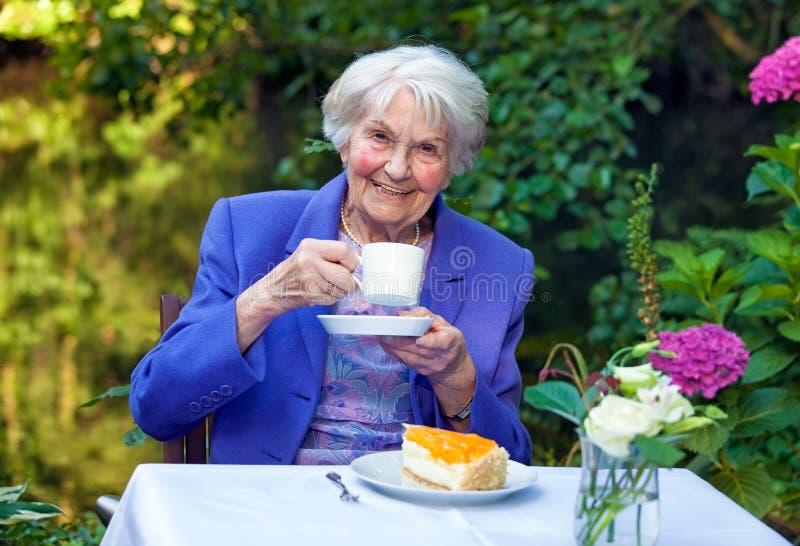 Lycklig hög kvinna i kaffe Tid på trädgården royaltyfri bild