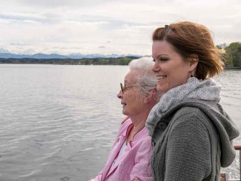 Lycklig hög kvinna med den unga dottern som ser sjön royaltyfri fotografi