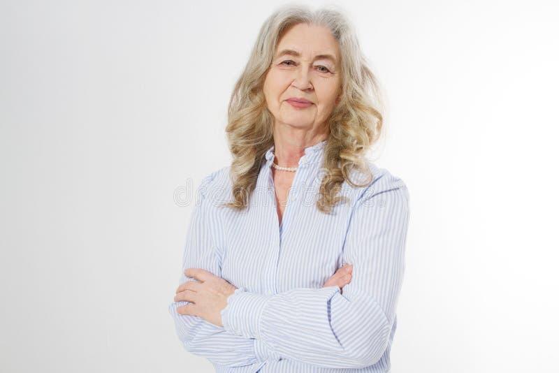 Lycklig hög kvinna med korsade armar på vit bakgrund Positiv äldre pensionärlivuppehälle och europeisk gammal skönhet royaltyfria bilder