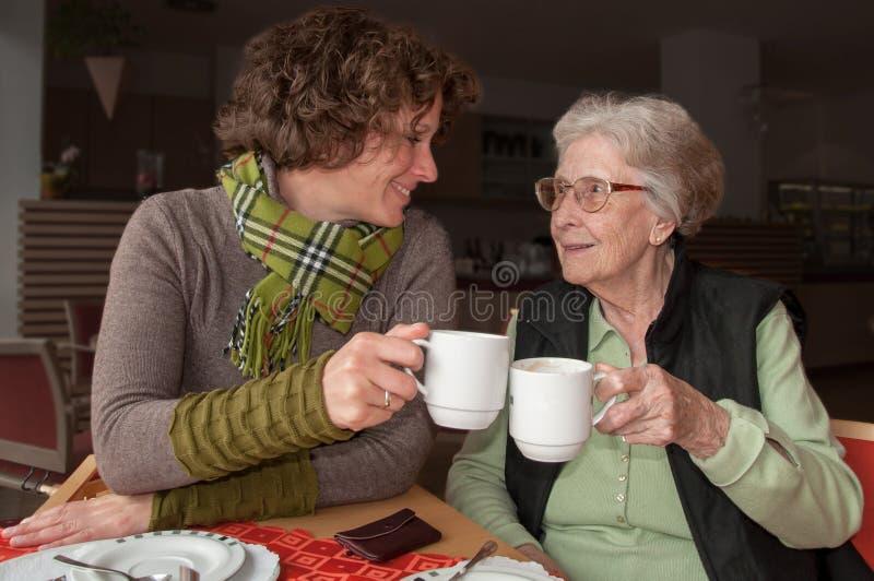 Lycklig hög kvinna och sondotter som dricker kaffe arkivbilder