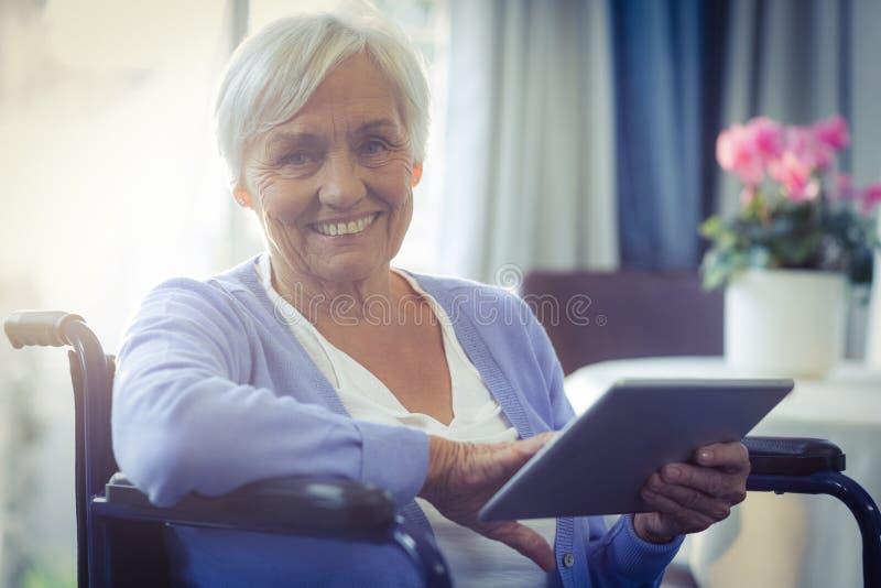 Lycklig hög kvinna på rullstolen genom att använda den digitala minnestavlan royaltyfri fotografi