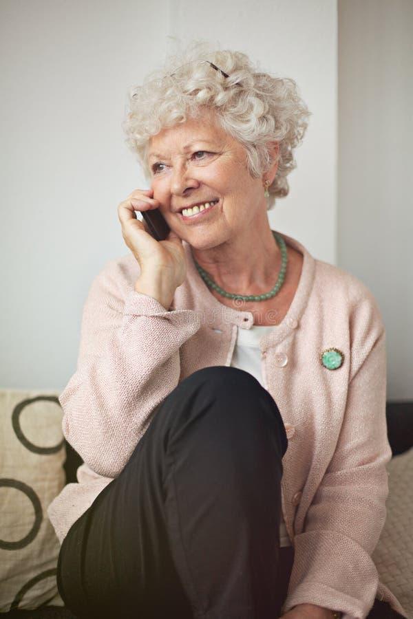 Lycklig hög kvinna på telefonen arkivfoto