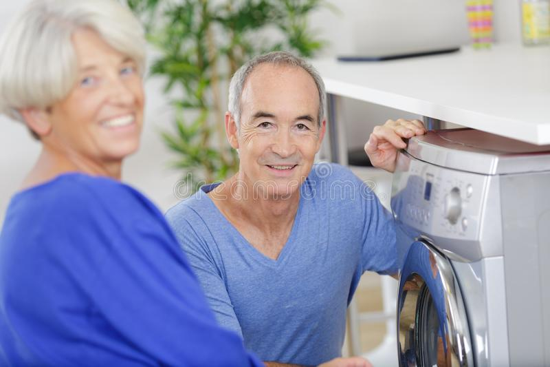Lycklig hög kvinna som ler stundmannen, i att använda tvagning-maskinen arkivfoto