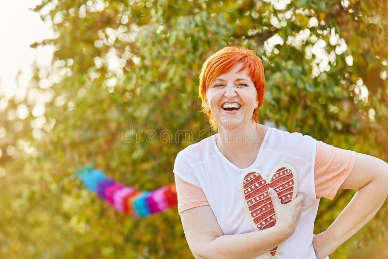 Lycklig hög kvinna som skrattar och rymmer en hjärta arkivfoto