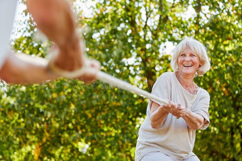 Lycklig hög kvinna som spelar dragkampen royaltyfri bild