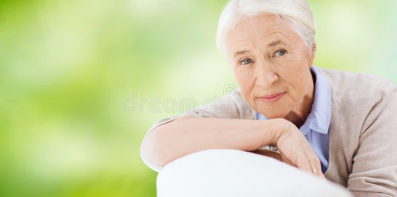 Lycklig hög kvinna som vilar på soffan arkivfoto
