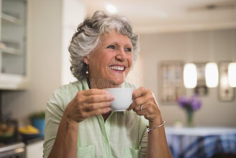 Lycklig hög kvinnainnehavkopp hemma royaltyfri fotografi