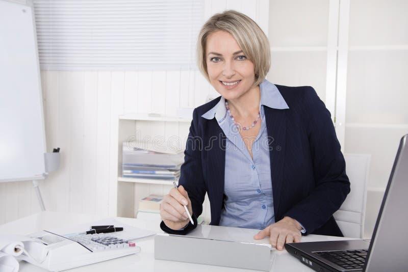 Lycklig hög kvinnlig chef - stående i kontoret. royaltyfria bilder