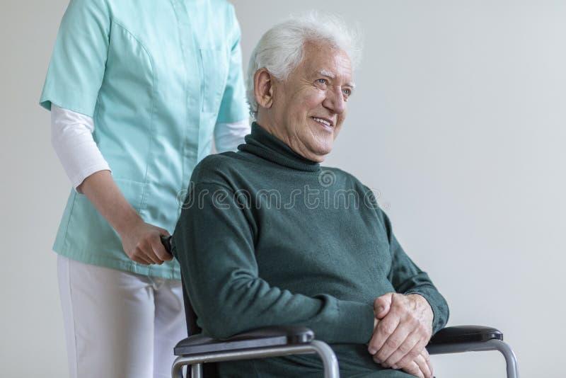 Lycklig hög man i rullstolen och sjuksköterskan som hjälper honom royaltyfri fotografi