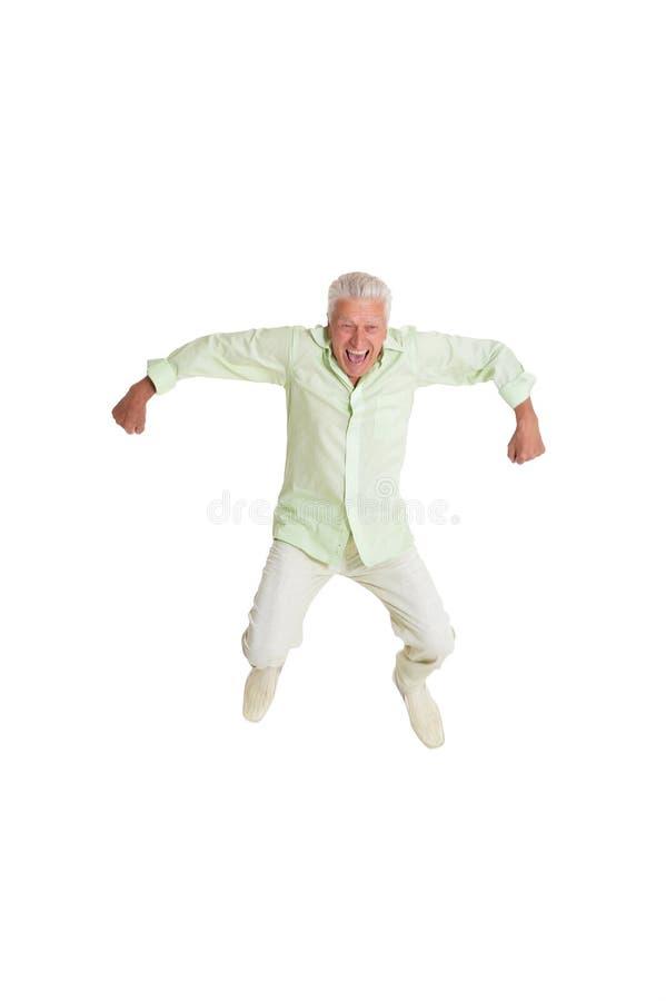 Lycklig hög man i skjorta som hoppar med händer upp fotografering för bildbyråer