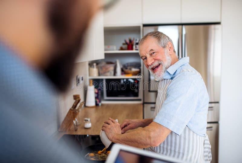 Lycklig hög man inomhus i kök hemma och att laga mat arkivbilder