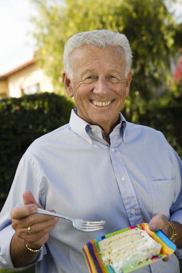 Lycklig hög man som äter kakan royaltyfri bild