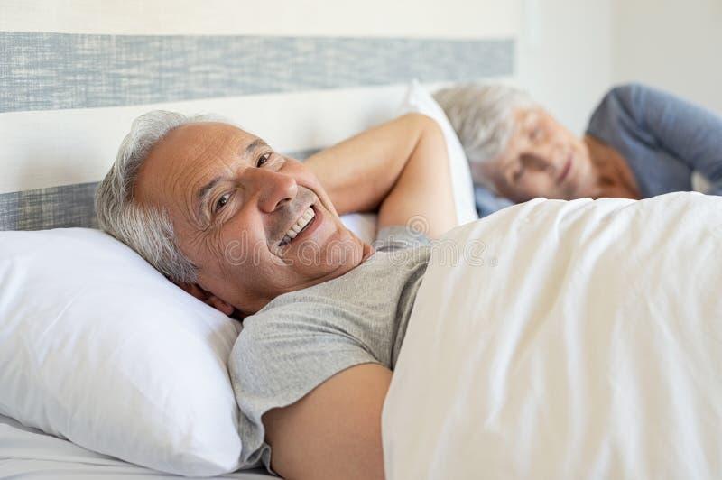 Lycklig hög man som ligger på säng royaltyfri foto