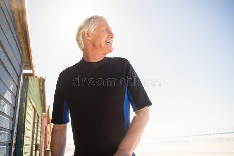 Lycklig hög man som ser bort, medan stå vid strandkojan arkivfoton