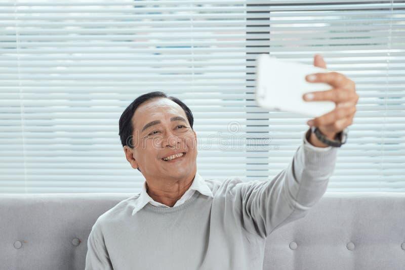 Lycklig hög man som visar Toothy leende, medan ta det Selfie fotoet genom att använda mobiltelefonen royaltyfria bilder