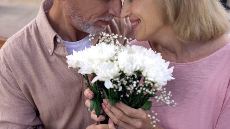 Lycklig hög nuzzling för par som tillsammans rymmer blommagruppen, årsdagdatum fotografering för bildbyråer