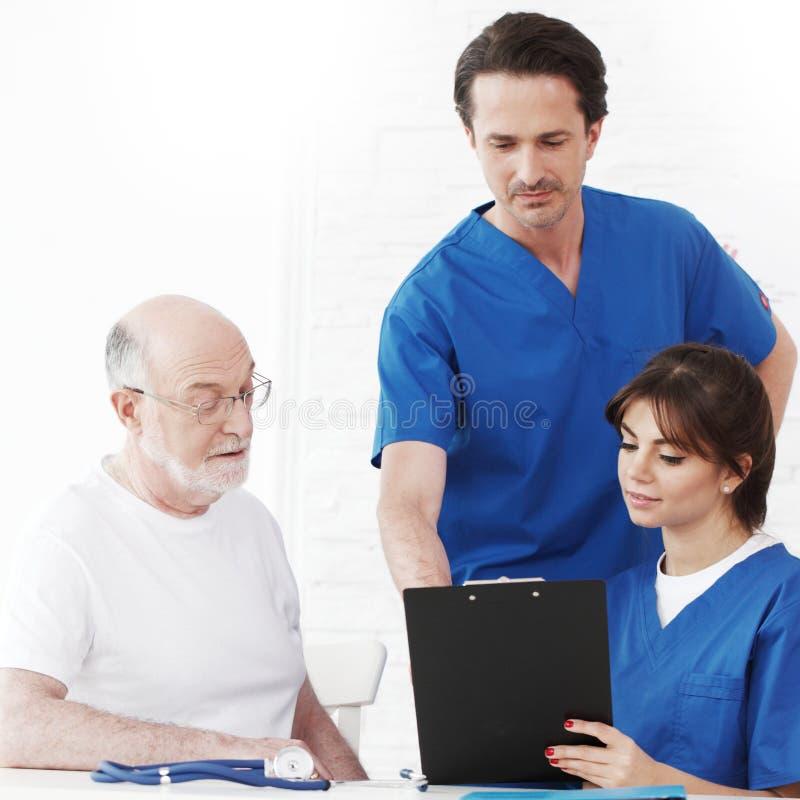 Lycklig hög patient och doktorer arkivbild