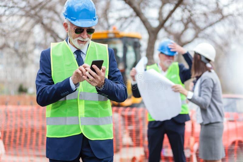 Lycklig hög tekniker eller affärsman som använder hans smarta telefon, medan kontrollera en konstruktionsplats royaltyfri bild