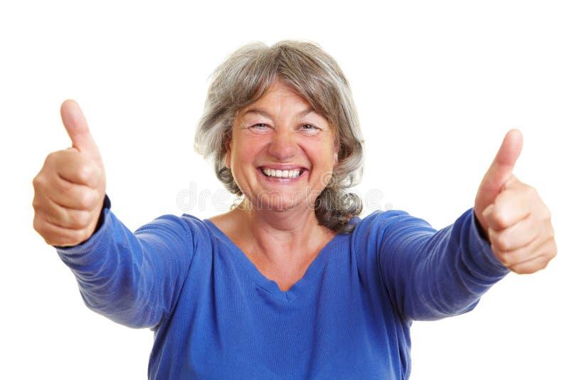 lycklig hög visande tumkvinna royaltyfri foto