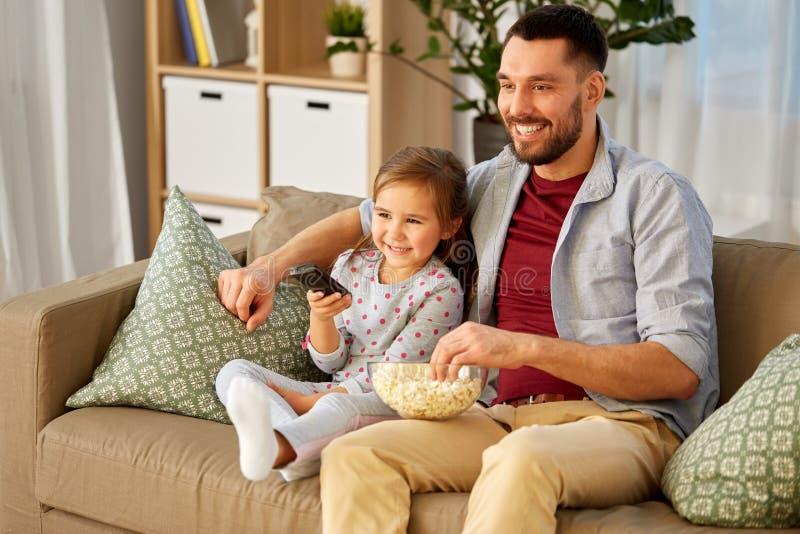 Lycklig h?llande ?gonen p? tv f?r fader och f?r dotter hemma arkivfoto