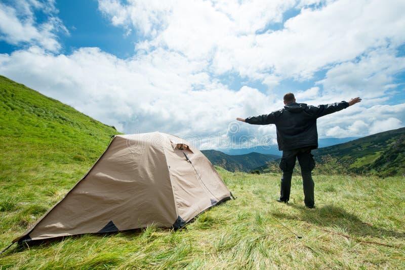 Lycklig handelsresande i bergen nära tältet arkivfoton