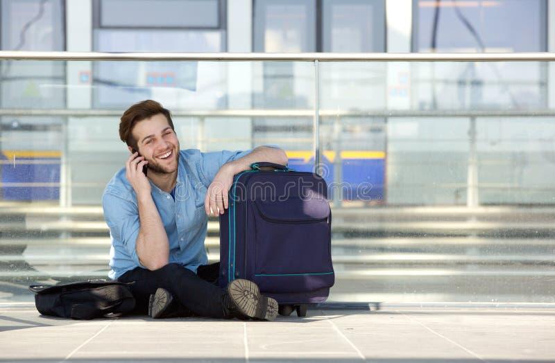 Lycklig handelsresande som väntar på stationen och talar på mobiltelefonen arkivfoto